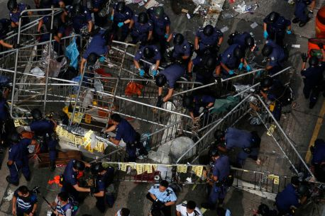 Police demolish a barricade set up by pro-democracy protesters at a protest site on the main Nathan Road at Mongkok district in Hong Kong, Nov. 26, 2014. Hong Kong police dismantled barricades, pulled down tents and cleared protesters from a demonstration site in the crowded Mong Kok district on Wednesday, Reuters witnesses said.
